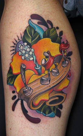 a piano,treble clef and some notes tattoo on lower leg.jpg